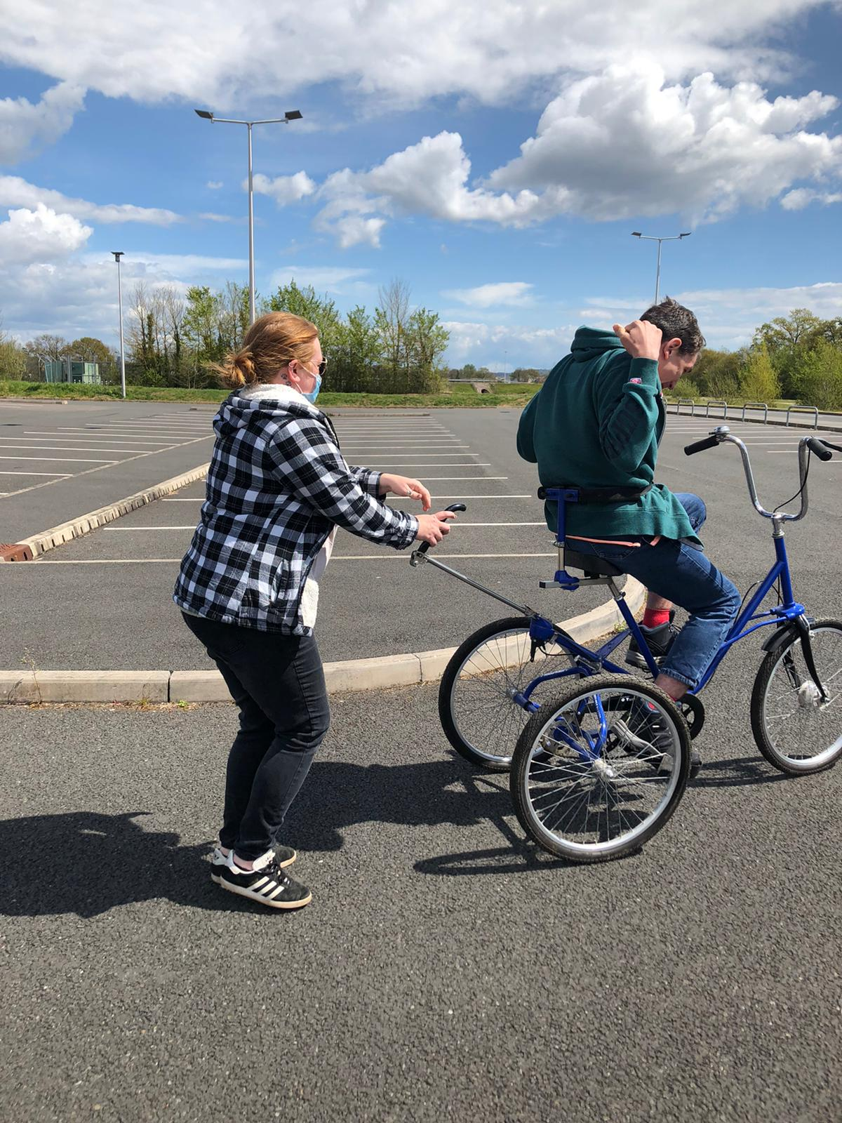 support worker helps James to drive tricycle