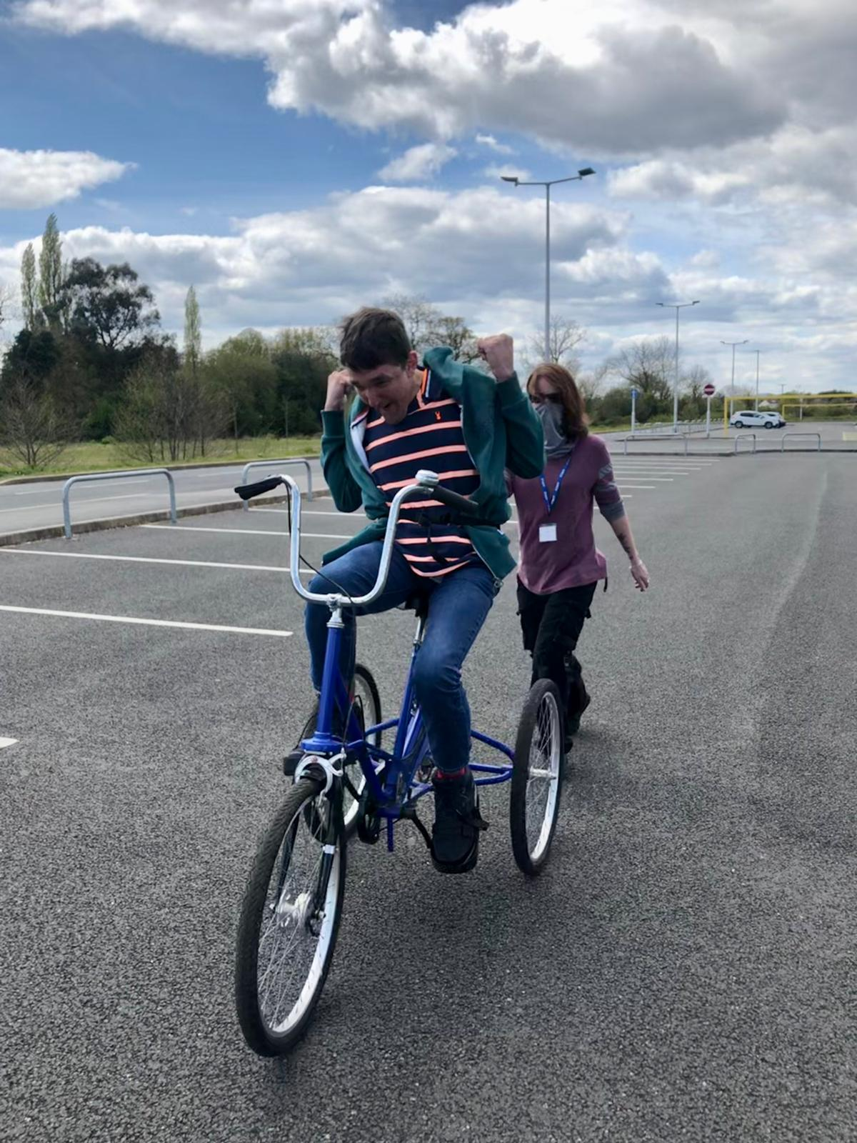 support worker helps James - Header to drive tricycle