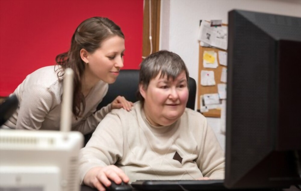 person with learning disability with support worker working on computer